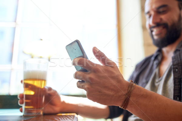 Homme smartphone bière pub personnes Photo stock © dolgachov