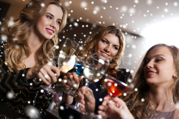 happy women with drinks at night club bar Stock photo © dolgachov