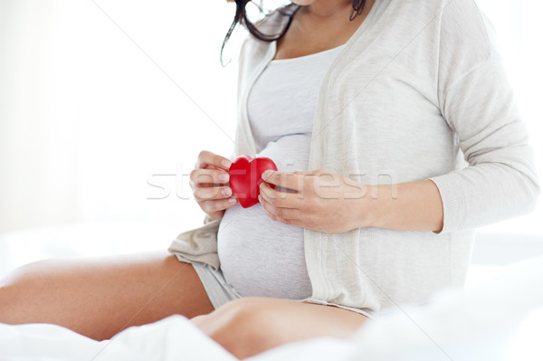 close up of pregnant woman with red heart in bed Stock photo © dolgachov