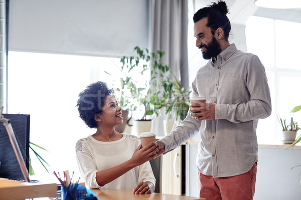 happy man bringing coffee to woman in office Stock photo © dolgachov