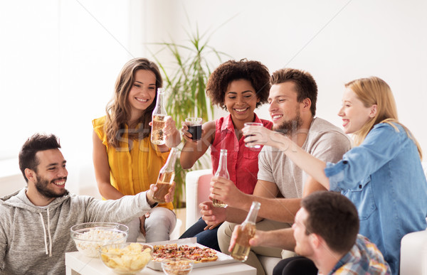 happy friends with drinks having party at home Stock photo © dolgachov
