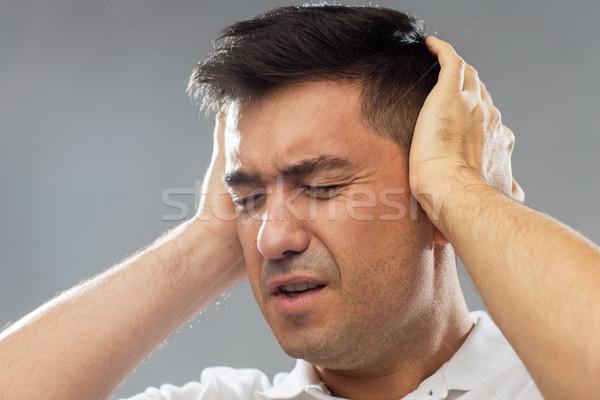 Hombre sufrimiento ruido orejas Foto stock © dolgachov