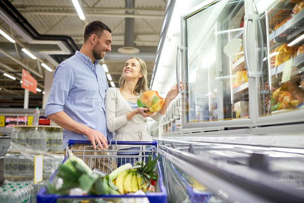 Couple With Shopping Cart Buying Food At Grocery Stock Photo