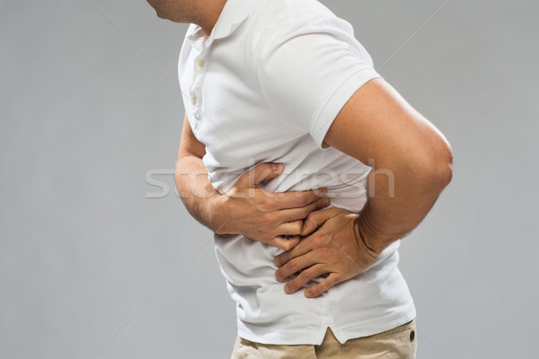 close up of man suffering from pain in side Stock photo © dolgachov