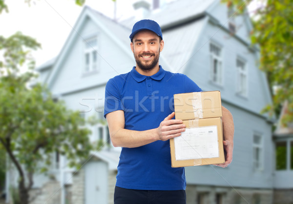 happy delivery man with parcel boxes Stock photo © dolgachov