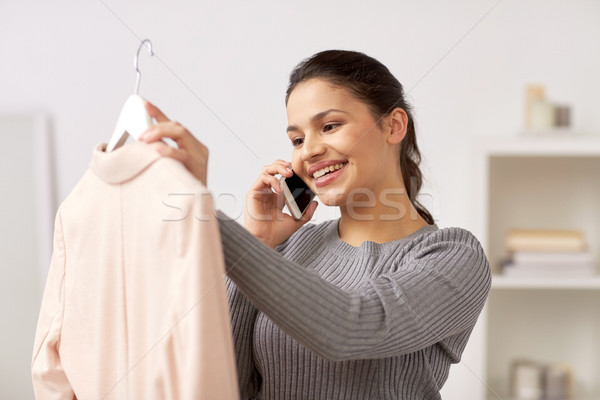 woman with jacket calling on smartphone at home Stock photo © dolgachov