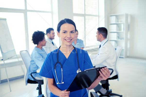 happy doctor with clipboard over group of medics Stock photo © dolgachov
