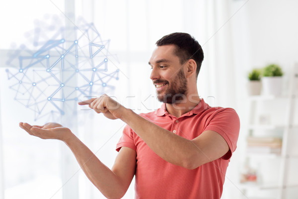 man with virtual polygonal projection at home Stock photo © dolgachov