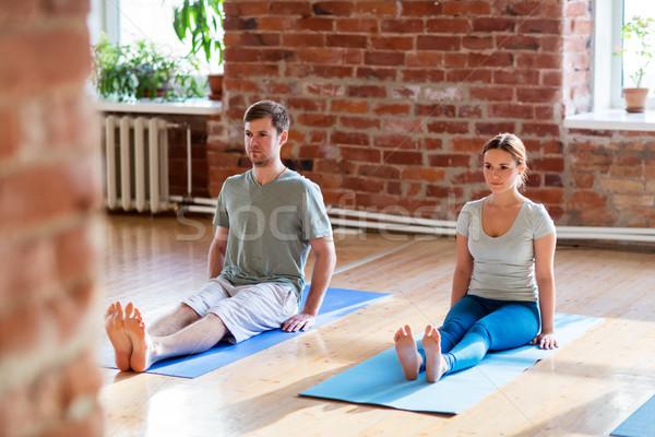 man and woman doing yoga staff pose at studio Stock photo © dolgachov