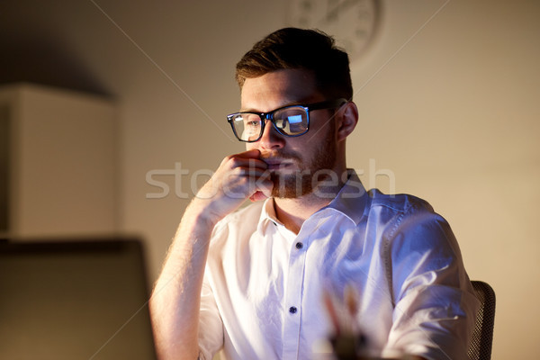 businessman in glasses with laptop at night office Stock photo © dolgachov