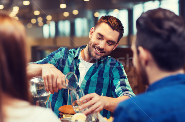 happy man with friends pouring water at restaurant Stock photo © dolgachov