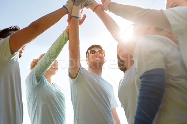 Stock photo: group of volunteers making high five outdoors