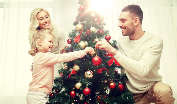 happy family decorating christmas tree at home Stock photo © dolgachov