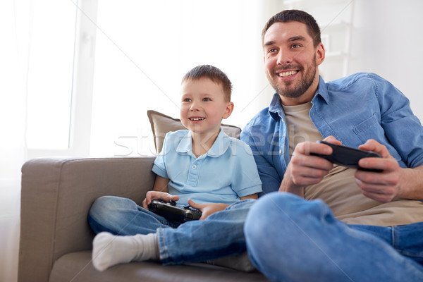 father and son playing video game at home Stock photo © dolgachov