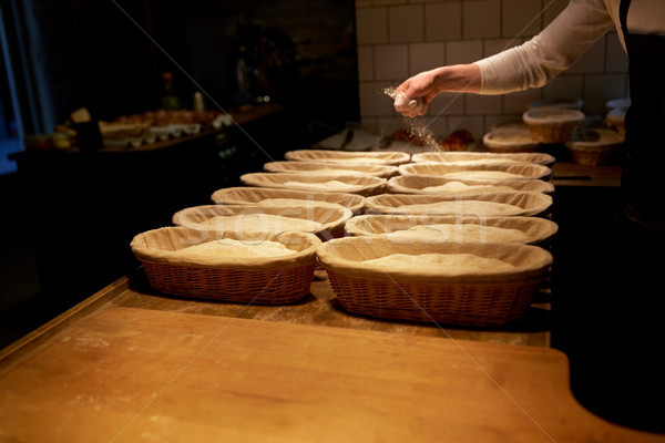 baker with baskets for dough rising at bakery Stock photo © dolgachov