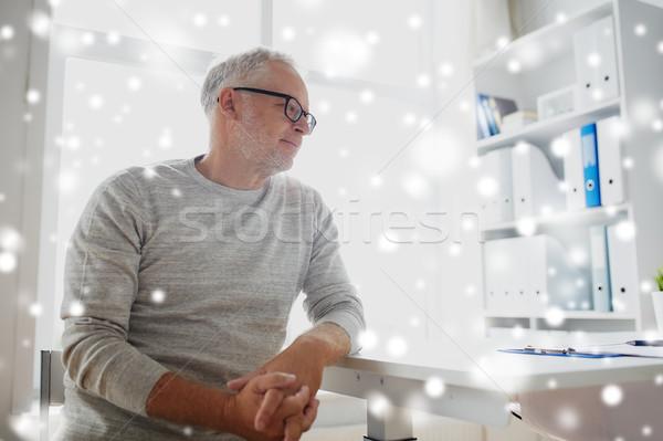 senior man sitting at medical office table Stock photo © dolgachov