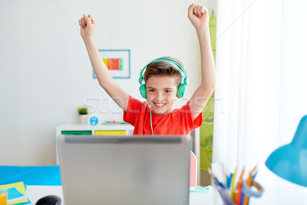 boy with headphones playing video game on laptop Stock photo © dolgachov