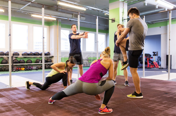 group of happy friends stretching in gym Stock photo © dolgachov