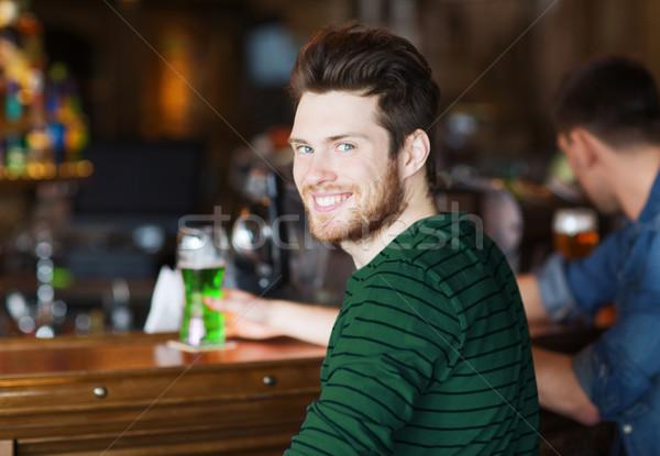 Szczęśliwy człowiek pitnej zielone piwa bar Zdjęcia stock © dolgachov
