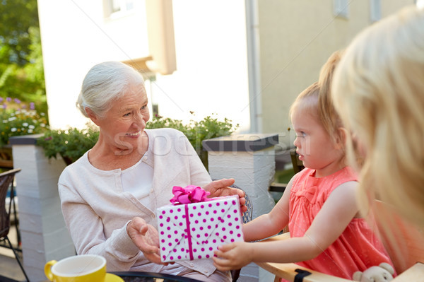 granddaughter giving present to grandmother Stock photo © dolgachov