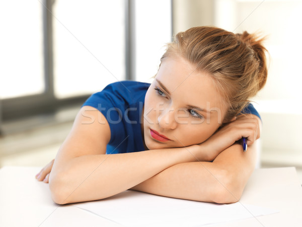 tired teenage girl with pen and paper Stock photo © dolgachov