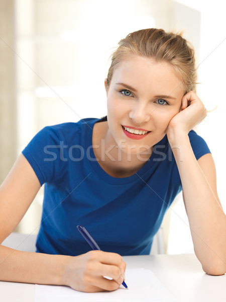 happy teenage girl with pen and paper Stock photo © dolgachov