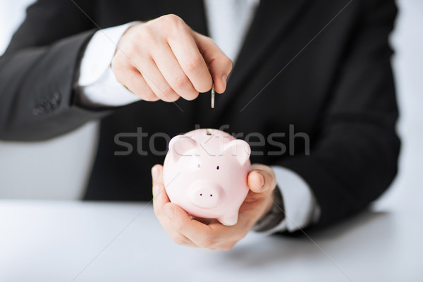 man putting coin into small piggy bank Stock photo © dolgachov