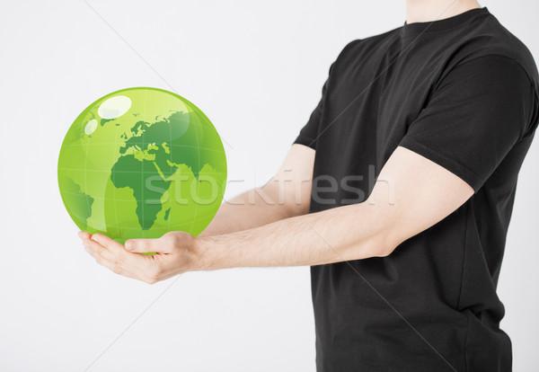 man holding green sphere globe Stock photo © dolgachov