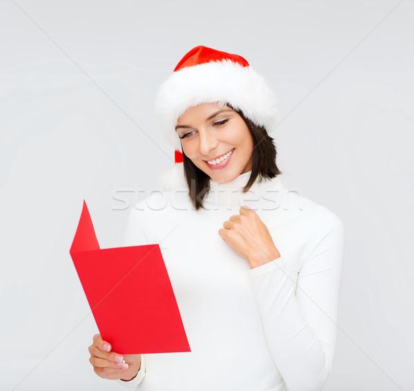woman in santa helper hat with blank red postcard Stock photo © dolgachov