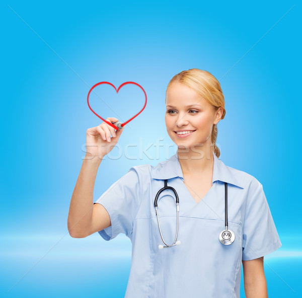 doctor or nurse drawing red heart Stock photo © dolgachov