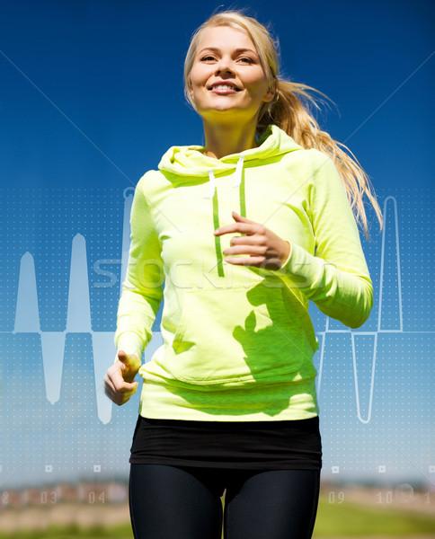 smiling woman jogging outdoors Stock photo © dolgachov