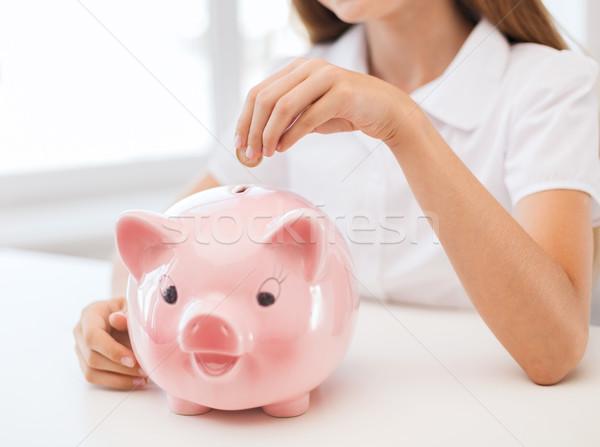 smiling child putting coin into big piggy bank Stock photo © dolgachov