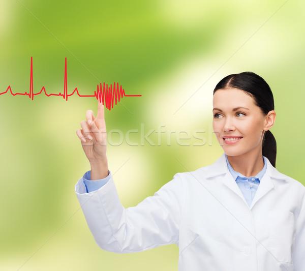 Sorridente feminino médico indicação cardiograma saúde Foto stock © dolgachov