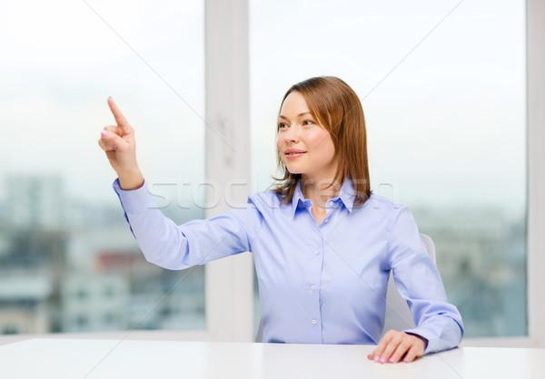 smiling woman pointing to something imaginary Stock photo © dolgachov
