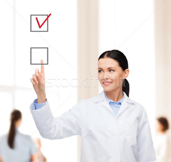 улыбаясь женщины врач указывая флажок здравоохранения Сток-фото © dolgachov