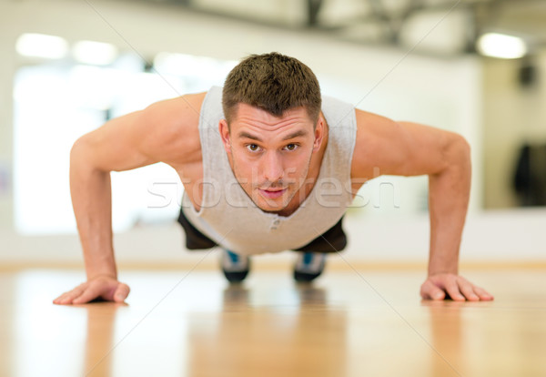 Stock photo: concentrated man doing push-ups in the gym