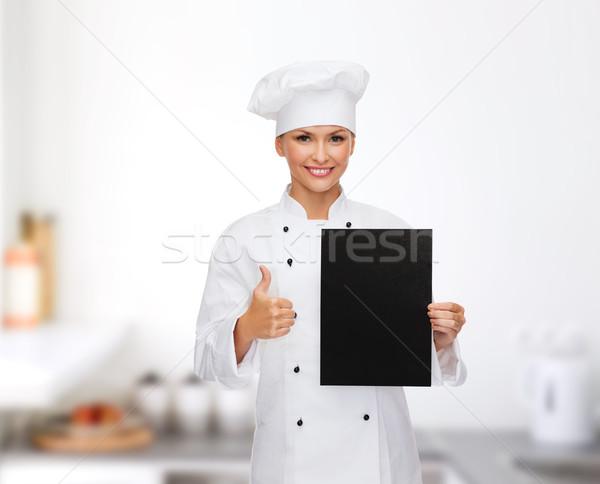 smiling female chef with black blank paper Stock photo © dolgachov
