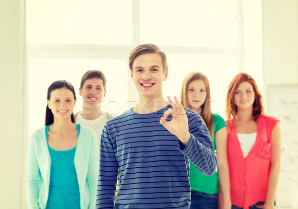 students with teenager in front showing ok sign Stock photo © dolgachov