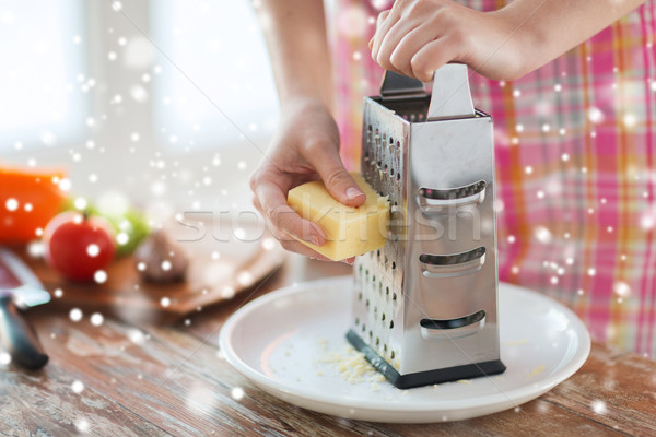 Stock photo: close up of woman hands with grater grating cheese