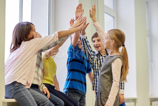 Groupe souriant école enfants high five Photo stock © dolgachov