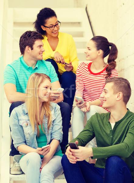 Souriant élèves smartphone discussion éducation école Photo stock © dolgachov