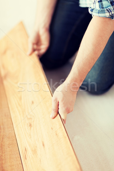 close up of male hands intalling wood flooring Stock photo © dolgachov