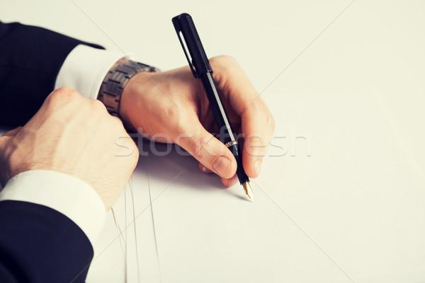Zakenman schrijven iets papier foto kantoor Stockfoto © dolgachov