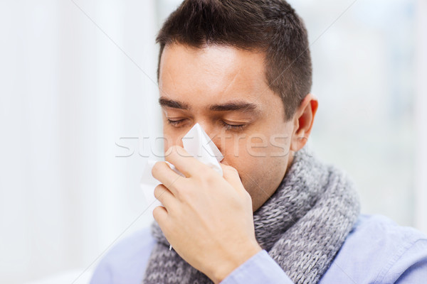 close up of ill man with flu blowing nose at home Stock photo © dolgachov