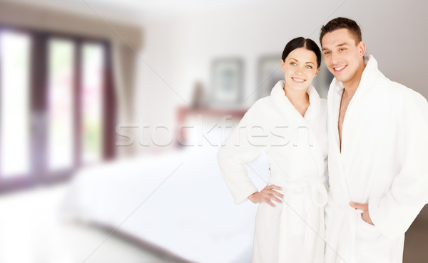 happy couple in bathrobes over spa hotel room Stock photo © dolgachov