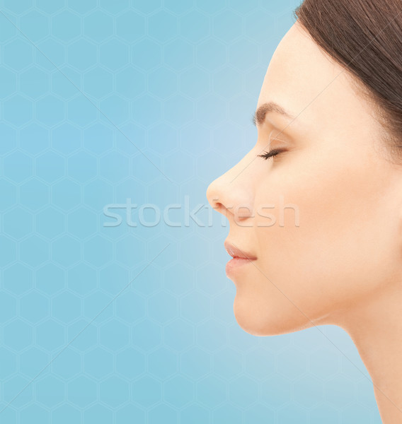 beautiful young woman face over blue background Stock photo © dolgachov
