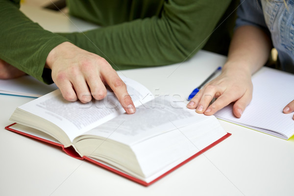 close up of students hands with book or textbook Stock photo © dolgachov