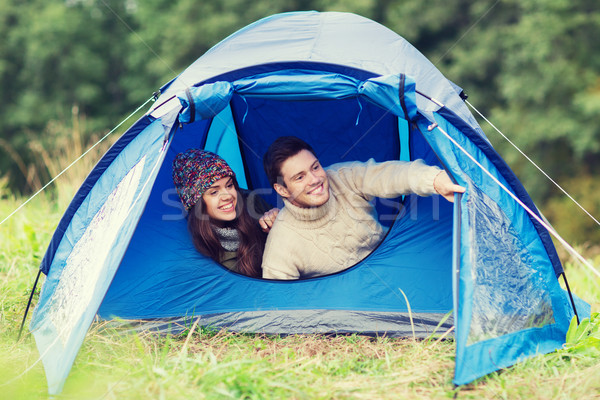 smiling couple of tourists looking out from tent Stock photo © dolgachov