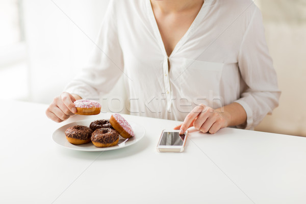 Stock photo: close up of hands with smart phone and donuts