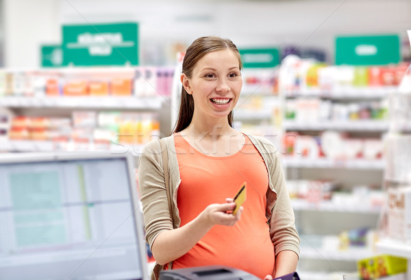 Stock photo: pregnant woman with credit card in drugstore